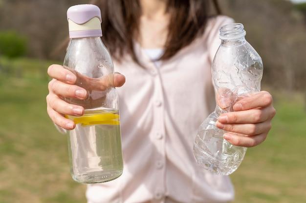 Nahaufnahmefrau, die glas- und plastikflaschen hält