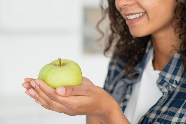 Nahaufnahmefrau, die grüne äpfel hält