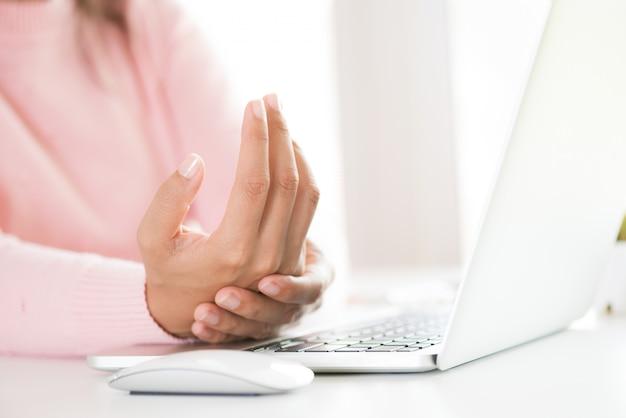 Nahaufnahmefrau, die ihre handgelenkschmerz von der anwendung des computers hält. büro-syndrom.