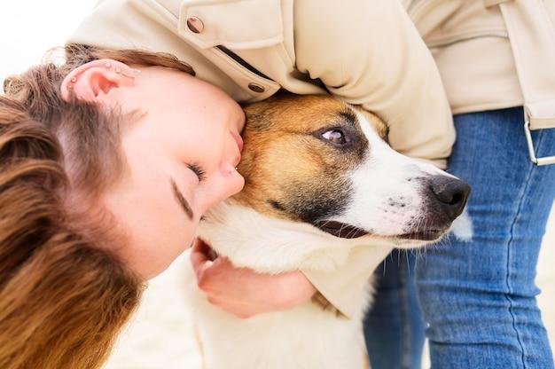 Nahaufnahmefrau, die ihren niedlichen hund umarmt