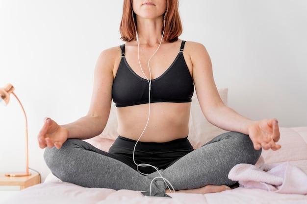 Nahaufnahmefrau, die im bett meditiert