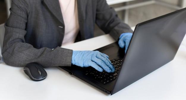 Nahaufnahmefrau, die im büro mit chirurgischen handschuhen arbeitet