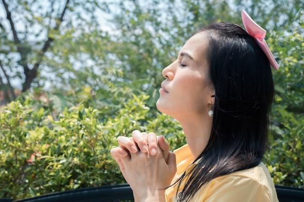 Nahaufnahmefrau, die im garten unter dem sonnenlicht betet.