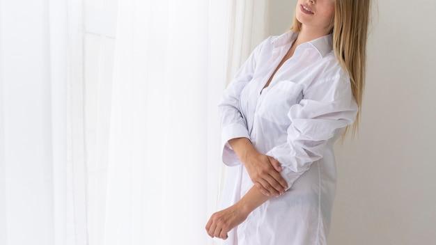 Nahaufnahmefrau, die im weißen hemd aufwirft