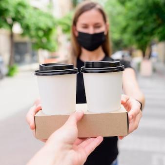 Nahaufnahmefrau, die kaffee zum mitnehmen empfängt