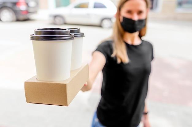 Nahaufnahmefrau, die kaffee zum mitnehmen liefert