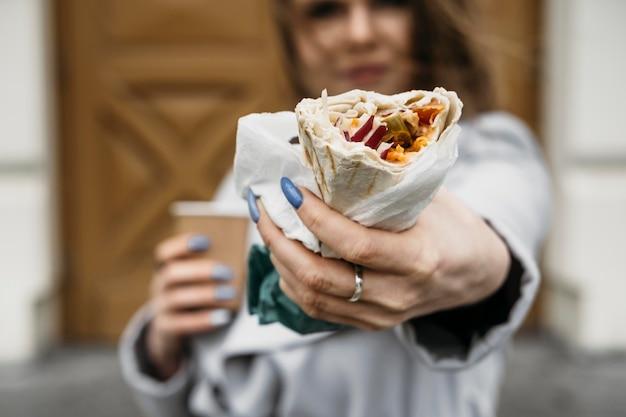 Nahaufnahmefrau, die kebab hält