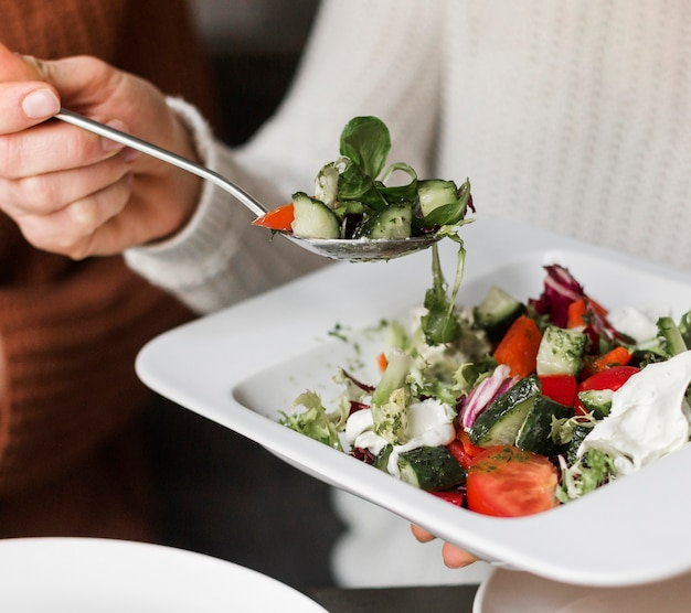 Nahaufnahmefrau, die köstlichen salat hat