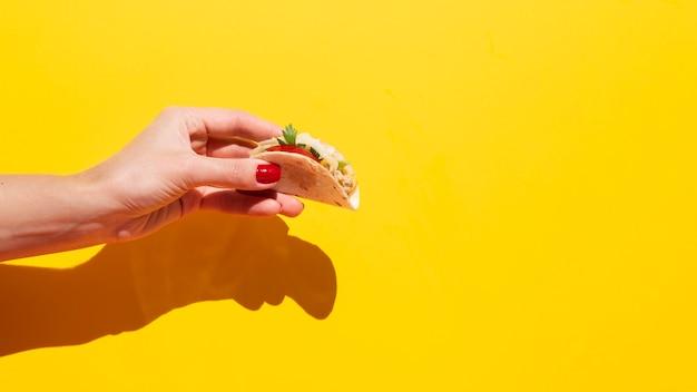 Nahaufnahmefrau, die köstlichen taco hält