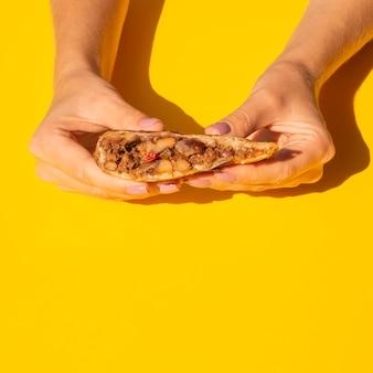 Nahaufnahmefrau, die köstliches mexikanisches lebensmittel hält