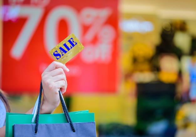 Nahaufnahmefrau, die kreditkarte und einkaufstaschen, black friday-verkaufskonzept hält