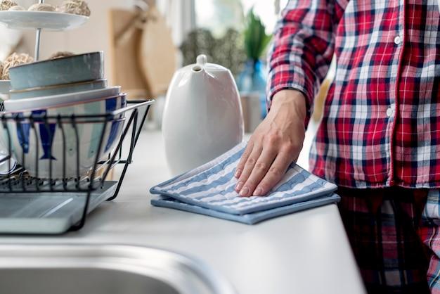 Nahaufnahmefrau, die küche mit stoff reinigt