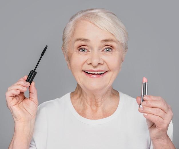 Nahaufnahmefrau, die lippenstift und wimperntusche hält