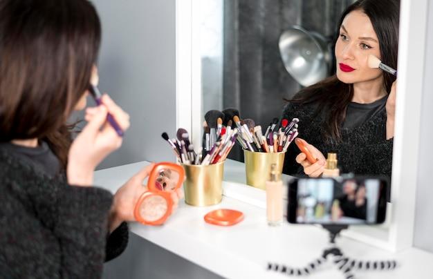 Nahaufnahmefrau, die make-up aufsetzt