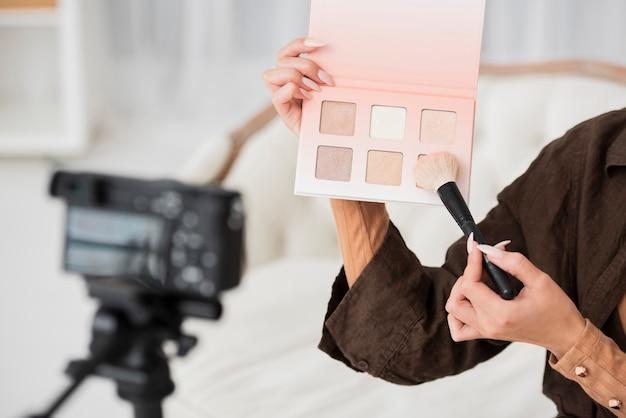 Nahaufnahmefrau, die make-upfarben hält