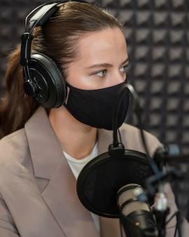Nahaufnahmefrau, die maske am radio s trägt