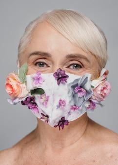 Nahaufnahmefrau, die maske mit blumen hält