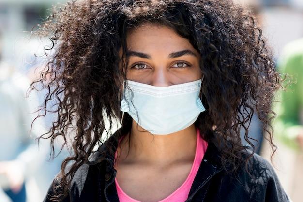 Nahaufnahmefrau, die medizinische maske in den straßen trägt