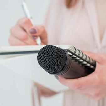Nahaufnahmefrau, die mikrofon hält und notizen schreibt