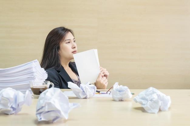Nahaufnahmefrau, die mit denkendem gesicht und einem weißbuch in ihrer hand arbeitet