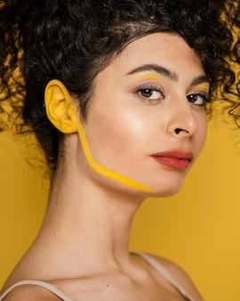 Nahaufnahmefrau, die mit gelbem make-up aufwirft