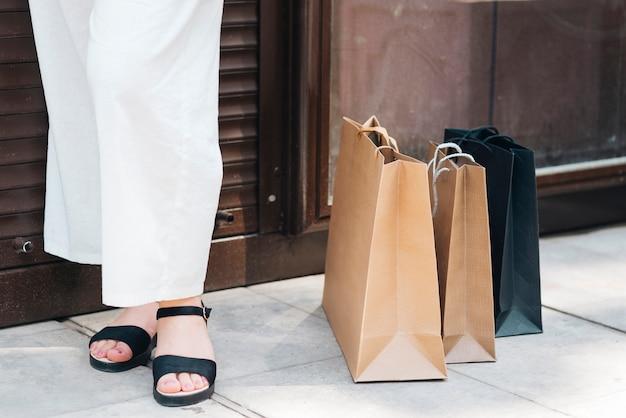 Nahaufnahmefrau, die nahe einkaufstaschen steht