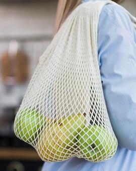 Nahaufnahmefrau, die öko-tasche mit bio-früchten hält