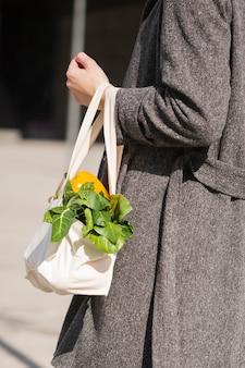 Nahaufnahmefrau, die ökologische tasche mit gemüse trägt