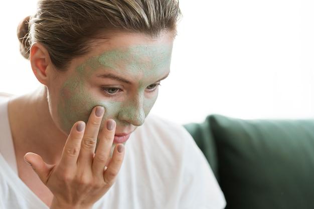 Nahaufnahmefrau, die organische gesunde gesichtsmaske verwendet