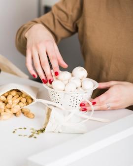 Nahaufnahmefrau, die organische pilze hält
