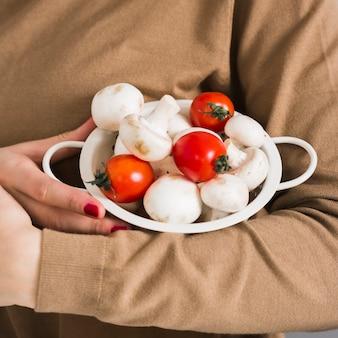 Nahaufnahmefrau, die organische pilze und tomaten hält