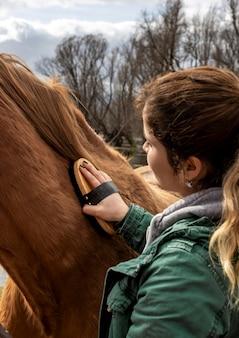 Nahaufnahmefrau, die pferd bürstet