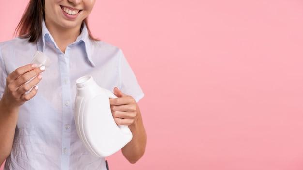 Nahaufnahmefrau, die reinigungsmittelwäscheflasche hält
