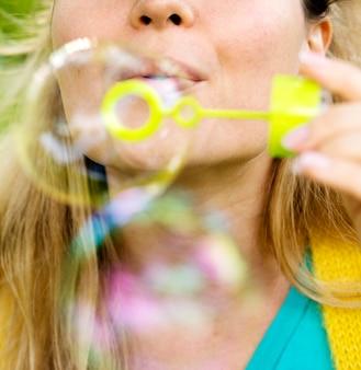 Nahaufnahmefrau, die seifenblasen macht