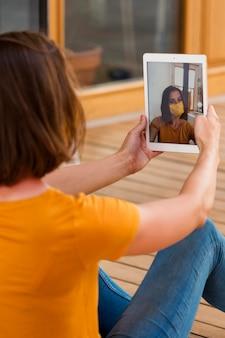 Nahaufnahmefrau, die selfie mit tablette nimmt