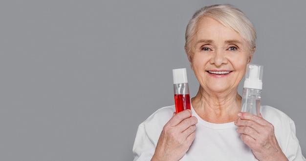 Nahaufnahmefrau, die serumflaschen hält