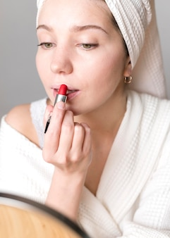 Nahaufnahmefrau, die spiegel verwendet, um lippenstift aufzutragen