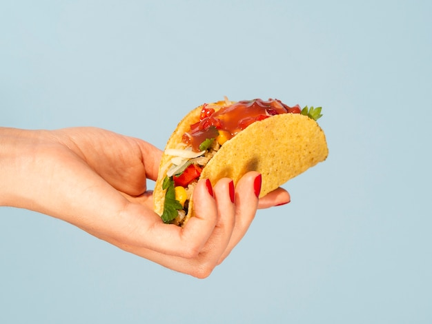 Nahaufnahmefrau, die taco mit blauem hintergrund hält