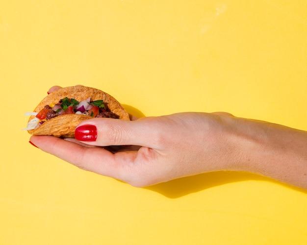Nahaufnahmefrau, die taco mit gelbem hintergrund hält