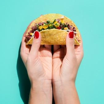 Nahaufnahmefrau, die taco mit grünem hintergrund hält