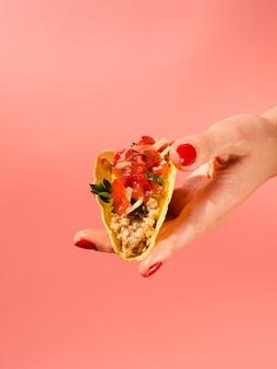 Nahaufnahmefrau, die taco mit rotem hintergrund hält