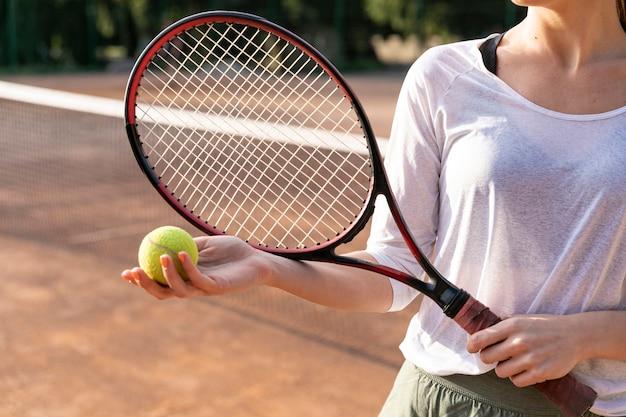 Nahaufnahmefrau, die tennisball hält