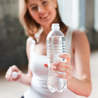 Nahaufnahmefrau, die wasserflasche hält