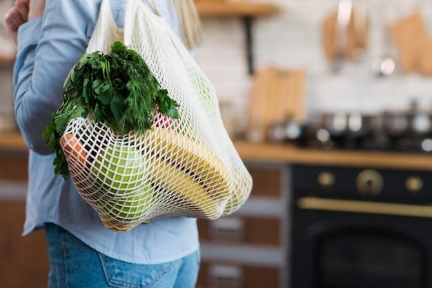 Nahaufnahmefrau, die wiederverwendbare tasche mit bio-lebensmitteln trägt