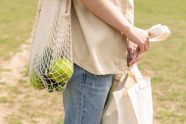 Nahaufnahmefrau, die wiederverwendbare taschen in der natur hält