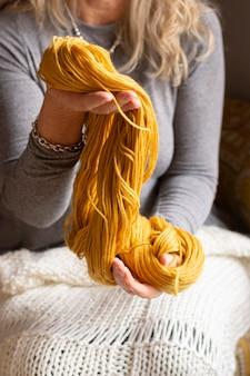 Nahaufnahmefrau, die wolle zum stricken hält