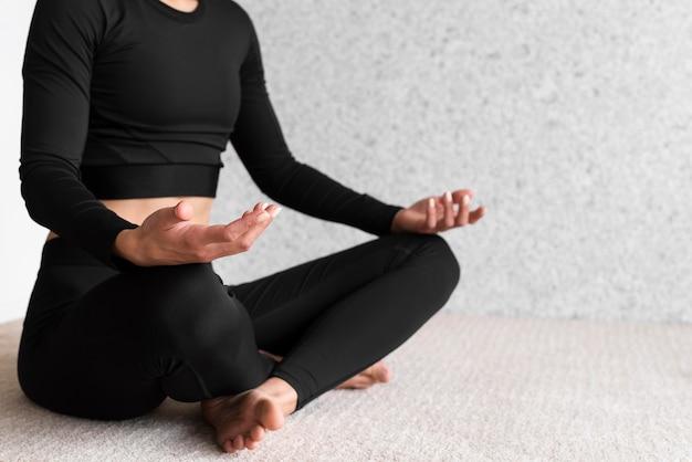 Nahaufnahmefrau, die yoga-pose tut