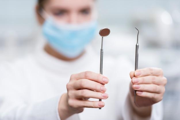 Nahaufnahmefrau, die zahnarztwerkzeuge hält