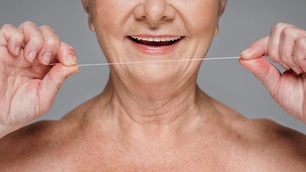 Nahaufnahmefrau, die zahnseide hält