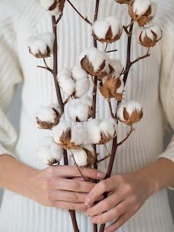 Nahaufnahmefrau, die zweige mit baumwollblumen hält